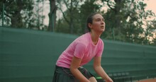 Young Tennis Player Backhand. Young Girl In Pink T-shirt Playing Lawn Tennis At Sunset. Eye Level