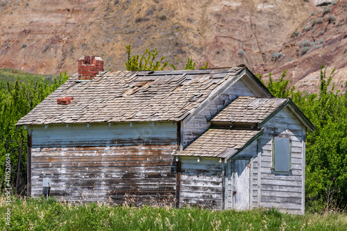 Canvas Print Vintage and deteriorating settlers homestead sits abandoned in a coulee in the b