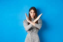 Serious Caucasian Woman In Dress Tell No, Show Cross Stop Gesture And Looking Confident, Making Warning Sign, Prohibit Something Bad, Standing On Blue Background