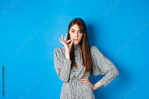 Vászonkép Serious woman promise to keep secret, seal lips, making zip gesture and looking