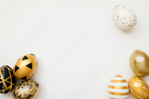 Fototapeta Easter golden decorated eggs isolated on white background. Minimal easter concept. Happy Easter card with copy space for text. Top view, flatlay obraz