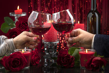 Male And Female Hands Clinking Glasses. Lit Red Candles In Transparent Candlesticks Illuminate A Bottle Surrounded By Roses On A Mirror Surface In Red Shining Bokeh Background. Valentine's Day 14