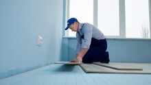DIY Repair, Professional Man In Work Suit And Cap On The Floor Lays The Laminate On A Blue Styrofoam Sheets In The New Room Near Window In Slow Motion