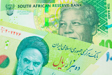 A Macro Image Of A Shiny, Green 10 Rand Bill From South Africa Paired Up With A Blue And Green Ten Thousand Rial Bank Note From Iran.  Shot Close Up In Macro.
