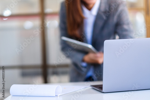 Closeup image of an asian business woman using digital tablet and laptop computer in office