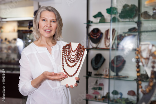 Obraz Woman offering to buy fashionable golden stone necklace in the shop of jewelry. High quality photo - fototapety do salonu