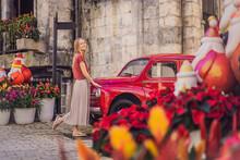 Elegant Portrait Of Beautiful Fashion Woman Wavy Shine Ginger Long Hair Beside Red Retro Car. Traveling In Europe After COVID-19 Coronavirus Quarantine Ends
