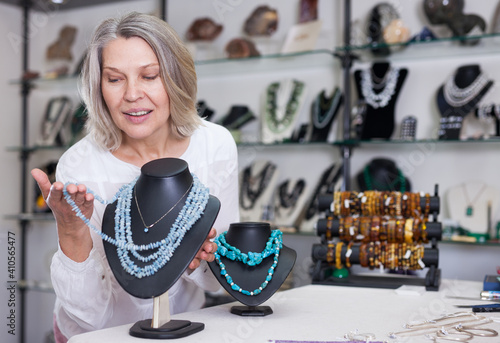 Fotografie, Obraz Woman trying on a turquoise necklace and earrings at a jewelry store