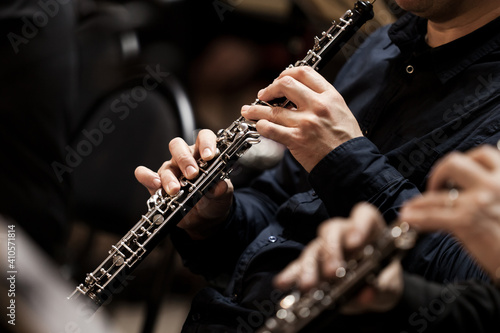 Leinwand Poster Hands of a musician playing the oboe in an orchestra