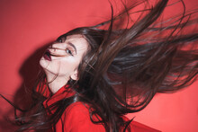 Crazy Girl Waving Her Hair. Woman With Stylish Makeup And Long Hair Posing In Total Red Outfit. Fashion Concept. Girl On Mysterious Face In Red Formal Jacket, Red Background.