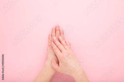 Slika na platnu Mature woman hands on light pink table background