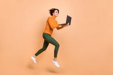 Full Length Photo Of Funky Sweet Girl Orange Turtleneck Communicating Modern Gadget Jumping Isolated Beige Color Background