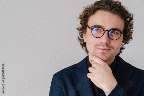 Obraz Pleased handsome man in eyeglasses posing and looking aside - fototapety do salonu