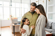 Happy Masculine Military Man Smiling And Hugging His Family Indoors
