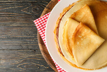 Board With Thin Pancakes On Wooden Background