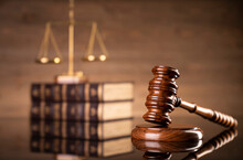 Law Symbols Composition On Brown Background. Gavel, Scale, Legal Books And Themis Sculpture. Place For Text.
