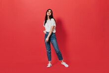 Beautiful Dark-haired Woman In Loose Jeans And White T-shirt Posing On Red Background