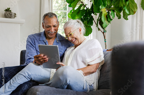 Photo Elderly couple using a tablet on a couch
