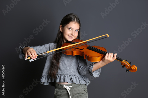Preteen girl playing violin on black background © New Africa