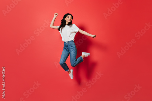 Mischievous girl in white T-shirt and jeans jumping on red background Fototapeta