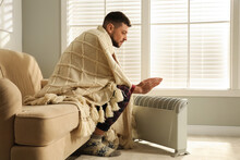 Man Warming Hands Near Electric Heater At Home