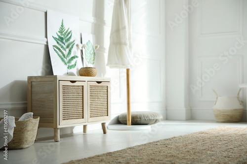 Wooden commode near white wall in room. Interior design