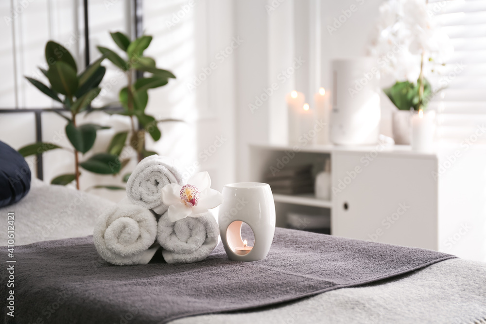 Fototapeta Towels, aroma lamp and orchid flower on couch in spa salon