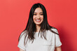 Lady with brown eyes is smiling on red background. Asian looking at camera