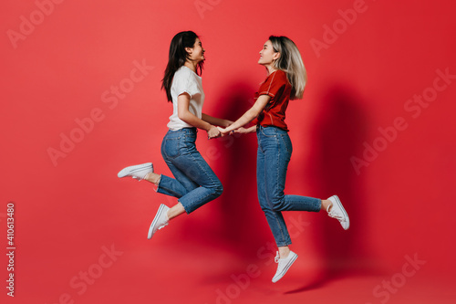 Fotografija Girls in jeans have fun and jump on red background