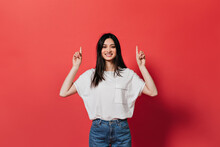 Asian Girl In Great Mood Is Showing Her Fingers Up To Place For Text On Red Background