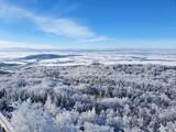 Zimowe, mroźne pejzaże w okolicy góry Ślęża. Niebieskie niebo i zamarznięte drzewa.