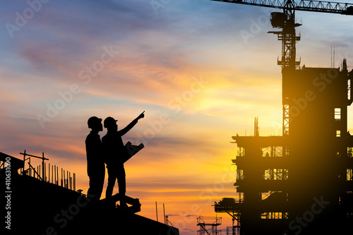 Obraz Silhouette of Engineer and worker checking project at building site background, construction site at sunset in evening time - fototapety do salonu