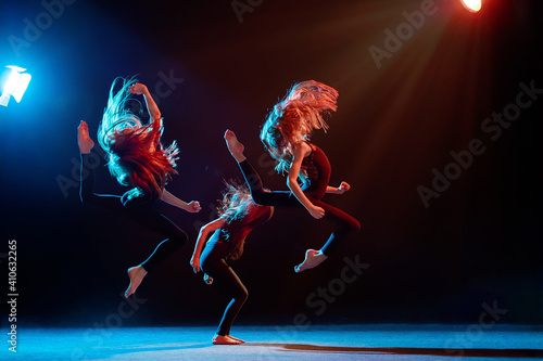 Foto group of three ballet girls in tight-fitting costumes jumping on black backgroun