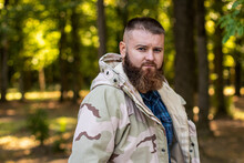 A Man With A Beard In A Military Jacket Looks At The Camera, In The Background Forest, Soft Focus