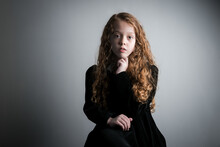Beautiful Young Girl In Black 1890s English Victorian 18th Century Child Period Dress With Elegant White Lace Collar Antique Broach Jewellery And Long Curly Pretty Hair Looking Straight At Camera