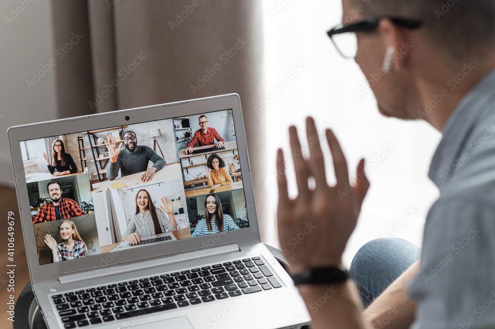 Fototapeta Group of diverse multiracial people on the laptop screen, a young man is waving hello to colleagues, employees online. Video conference, brainstorm, webinar concept