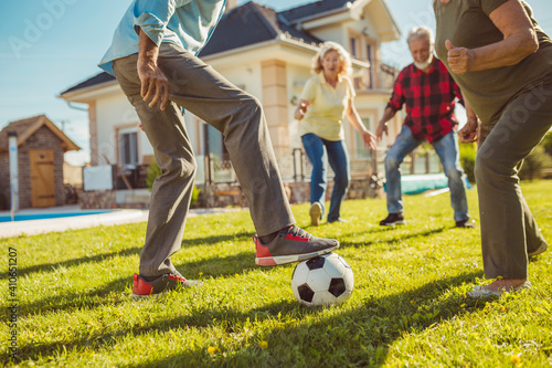 Obraz Elderly friends having fun playing football on a sunny summer day - fototapety do salonu