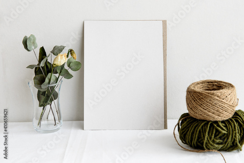 Fototapeta Fashion wedding stationery mockup scene. An empty vertical greeting card and dried white flowers on a white linen background. Feminine still life, top view. obraz