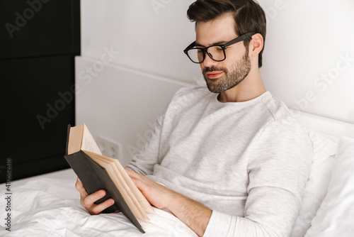 Focused young man in eyeglasses reading book while resting in bed