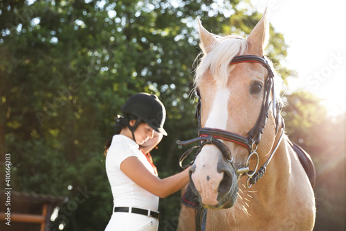 Fotografia, Obraz Young woman in horse riding suit and her beautiful pet outdoors on sunny day