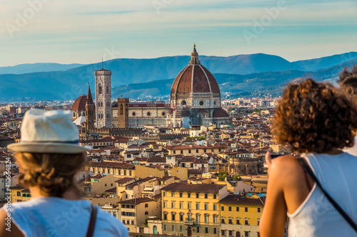 Cuadros en Lienzo Two women admiring the panoramic view from the square Piazzale Michelangelo to the historic heart of Florence with the Cathedral Santa Maria del Fiore and the Giotto's Campanile in the centre at dusk