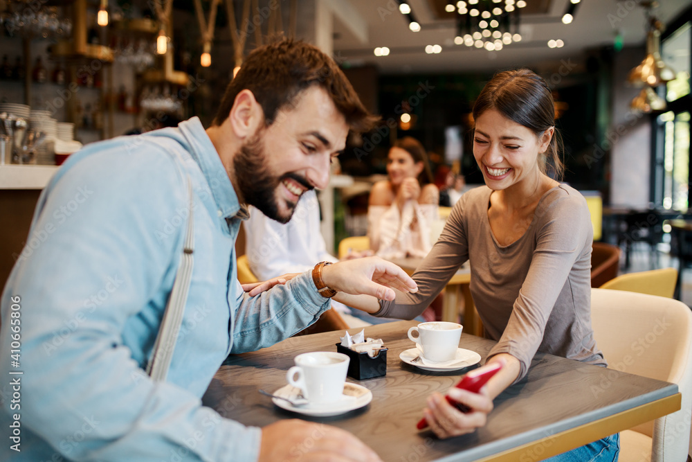 Fototapeta Young happy couple using smartphone in cafe