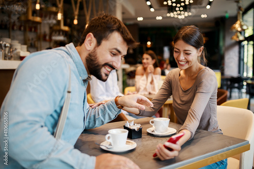 Obraz Young happy couple using smartphone in cafe - fototapety do salonu
