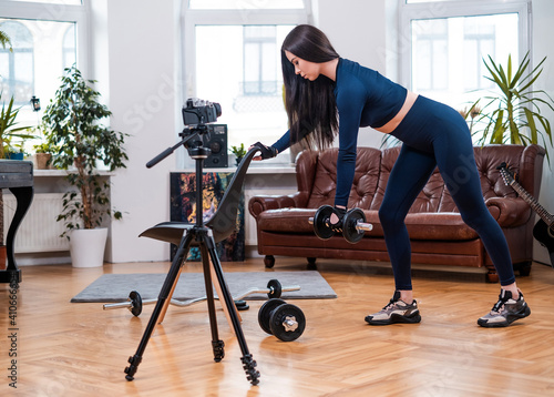 Modern living room with styled furniture and female athlete which poses on camera doing physical exercise with chair and dumbell Fototapete