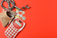 Rosary With Coins In S Gunny Sack And Calculator On Red Background. Islamic Banking Or Finance Concept. Top View And Selective Focus.