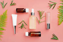 Glass And Plastic Cosmetic Bottles On Pink Background With Fern And Rosemary Leaves