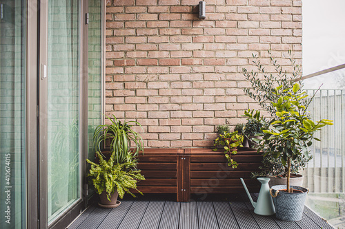 Fototapeta Morden residential balcony garden with bricks wall, wooden bench and plants