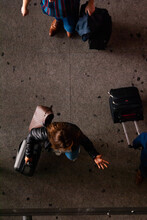 Aerial View, Looking Down At The Airport. Woman With Luggage And Hand Gesture