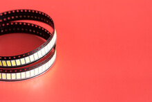 Yellow Led Strip Coil Packaging Closeup Isolated On Red Background. Spare Part For Repair Lamp Or Latern. Diode Tape In The Package.