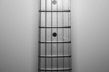 Black And White Close Up Of Guitar Neck With Frets And Strings